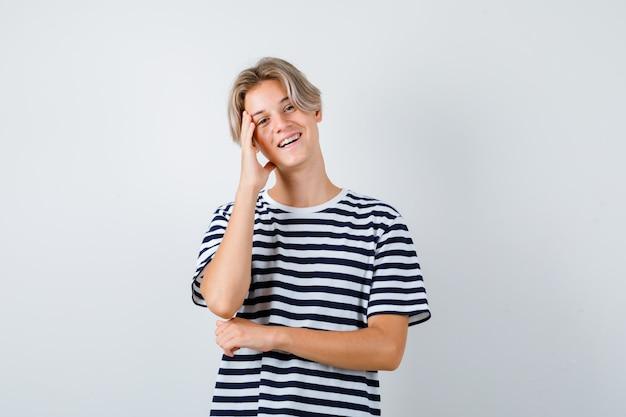 Teen chłopiec trzymając rękę na głowie, uśmiechając się w t-shirt i patrząc radosny, widok z przodu.