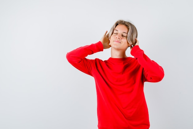 Teen chłopiec trzymający ręce na głowie, zamykający oczy w czerwonym swetrze i wyglądający uroczo. przedni widok.