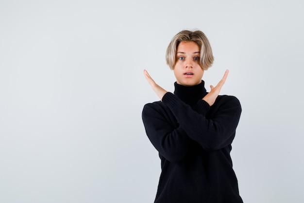 Teen chłopiec w czarnym swetrze pokazując gest stop ze skrzyżowanymi rękami i patrząc zaskoczony, widok z przodu.
