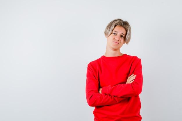 Teen chłopiec w czerwonym swetrze z rękami skrzyżowanymi i patrząc niezadowolony, widok z przodu.
