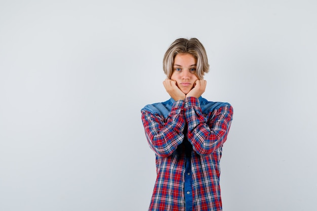 Teen chłopiec w kraciastej koszuli podpierając podbródek na rękach i patrząc ostrożnie, widok z przodu.