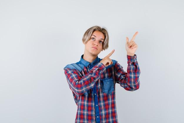 Teen chłopiec w kraciastej koszuli, wskazując na bok i patrząc zamyślony, widok z przodu.