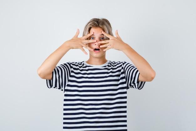 Teen chłopiec w t-shirt patrząc przez palce i patrząc zaskoczony, widok z przodu.