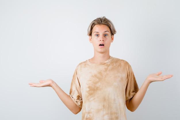 Teen chłopiec w t-shirt pokazując bezradny gest, otwierając usta i patrząc w szoku, widok z przodu.