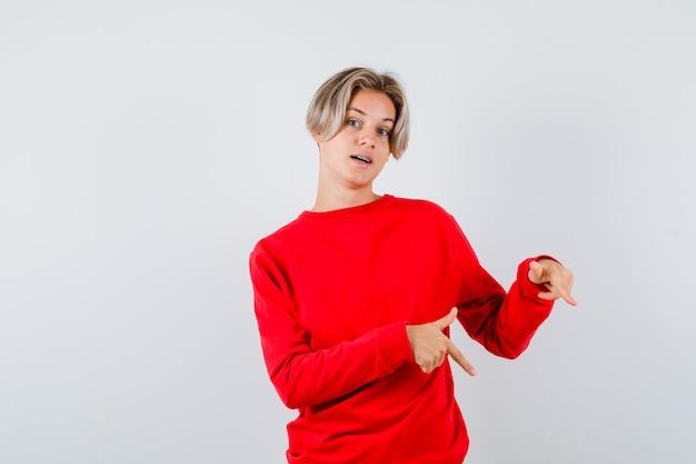 Teen chłopiec wskazując w dół w czerwonym swetrze i patrząc zaskoczony, widok z przodu.