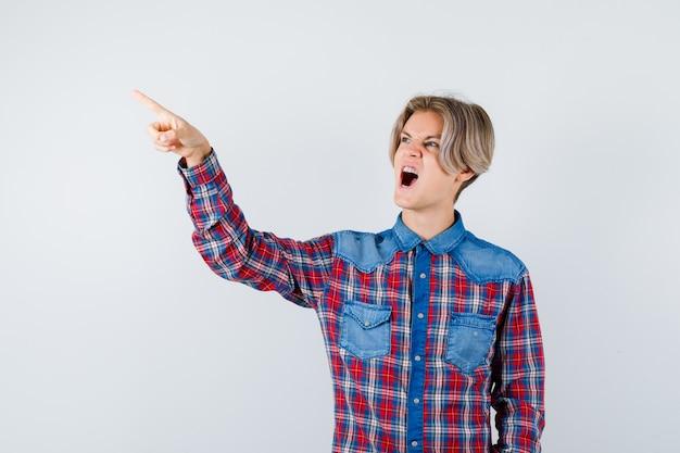 Teen chłopiec wskazujący w kraciastą koszulę i patrząc zirytowany, widok z przodu.