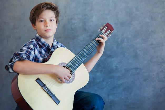 Teen chłopiec z gitarą akustyczną