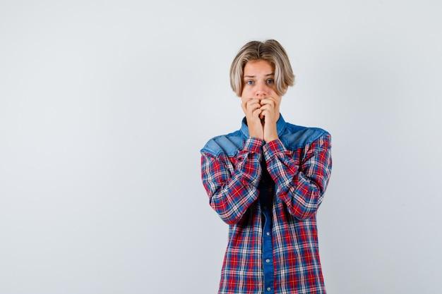 Teen chłopiec z rękami na rękach w kraciastej koszuli i patrząc niespokojny, widok z przodu.