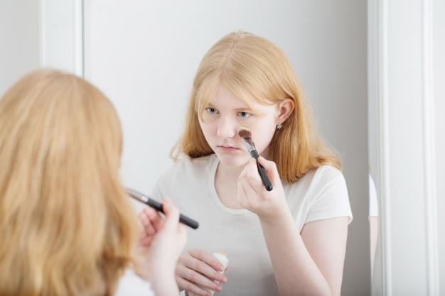 Teen dziewczyna bada trądzik na twarzy przed lustrem