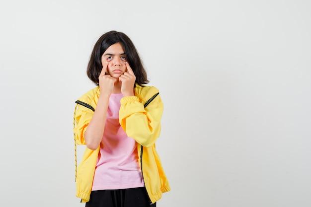 Teen dziewczyna ciągnąc oczy palcami w żółtym dresie, koszulce i patrząc na zmęczoną, widok z przodu.