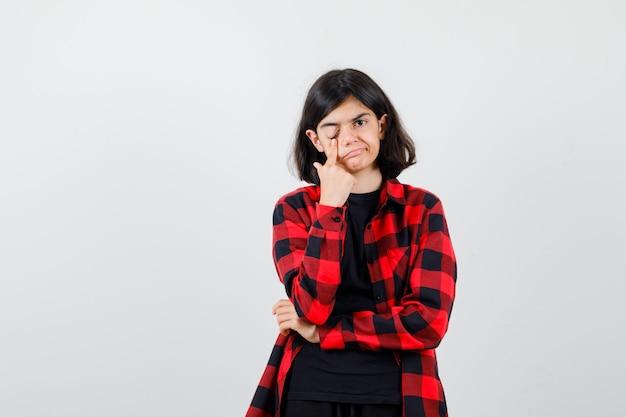 Teen dziewczyna ciągnąc powiekę w t-shirt, koszulę w kratkę i patrząc niezadowolony, widok z przodu.