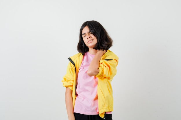 Teen dziewczyna cierpi na ból szyi w koszulce, kurtce i źle wygląda, widok z przodu.