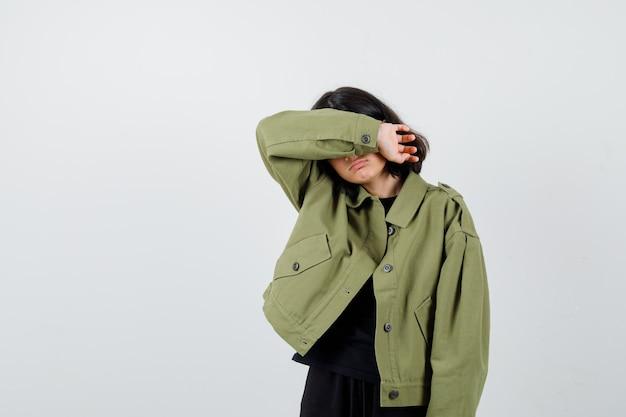 Teen dziewczyna cierpi na silny ból głowy w wojskowej zielonej kurtce i wygląda na przygnębioną. przedni widok.