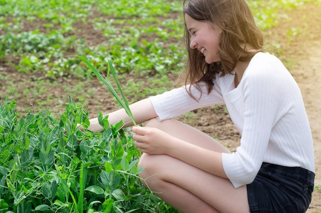 Teen dziewczyna dotyka rąk z zielonymi roślinami w ogrodzie