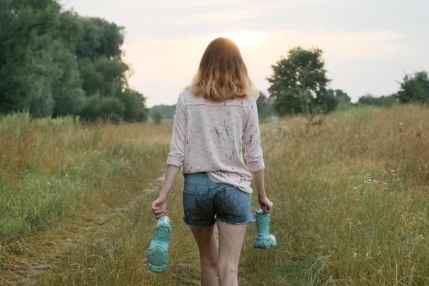 Teen dziewczyna idzie na wiejskiej drodze z butami w ręce