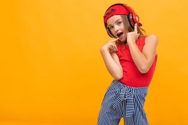 Teen dziewczyna lubi muzykę na słuchawkach i tańczy na żółtym tle z miejsca na kopię.