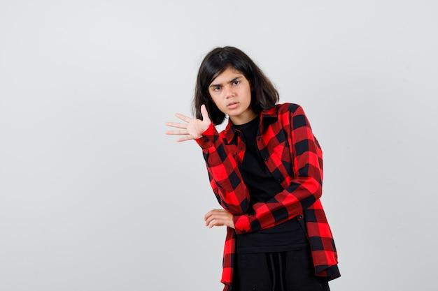 Teen dziewczyna macha ręką na powitanie w casual shirt i patrząc zamyślony. przedni widok.