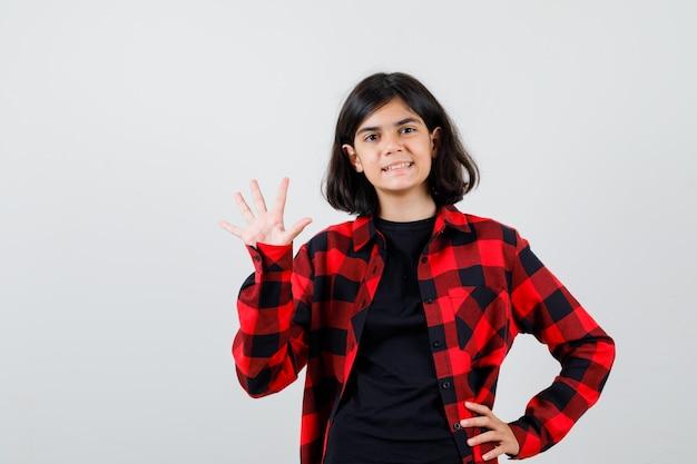 Teen dziewczyna macha ręką na powitanie w t-shirt, kraciaste koszule i patrząc radosny. przedni widok.