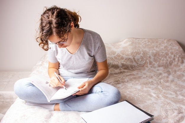 Teen dziewczyna na łóżku studiuje w domu z powodu kwarantanny