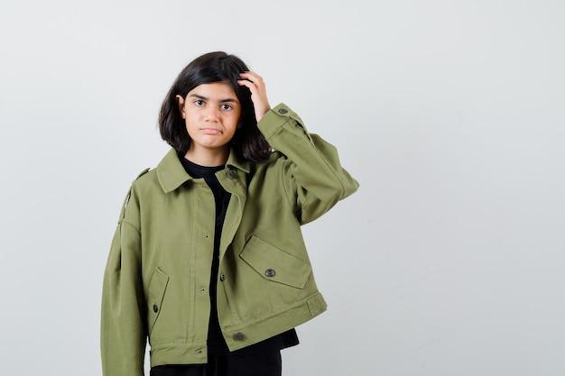 Teen dziewczyna patrząc na kamery podczas drapania się po głowie w t-shirt, zielona kurtka i patrząc niezdecydowany, widok z przodu.