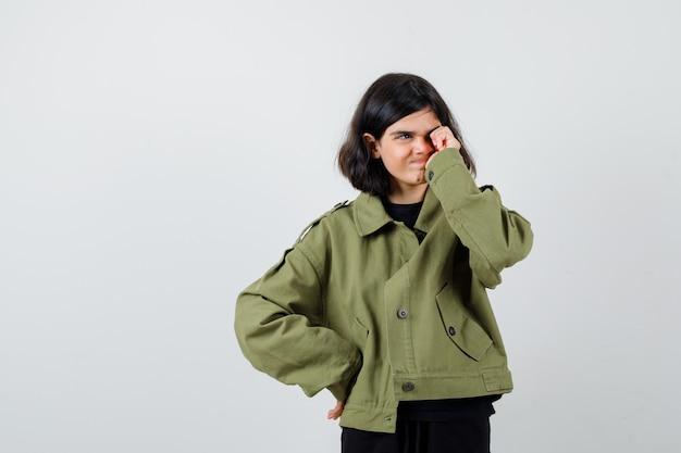 Teen dziewczyna pocierając oko, odwracając wzrok w zielonej kurtce i patrząc zamyślony. przedni widok.