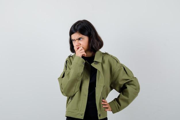 Teen dziewczyna podpierając podbródek pod ręką w koszulce, zielonej kurtce i patrząc poważnie, widok z przodu.