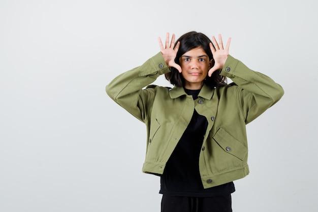 Teen dziewczyna pokazuje gest kapitulacji w zielonej kurtce i wygląda pewnie. przedni widok.