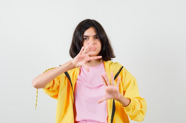 Teen dziewczyna pokazuje gest stop w żółtym dresie, koszulce i patrząc tęsknie, widok z przodu.