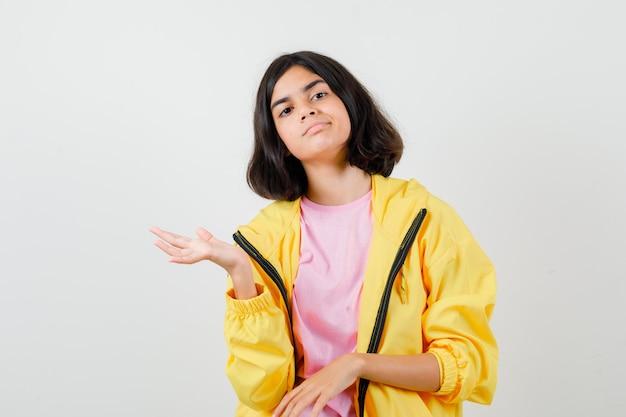 Teen dziewczyna pokazuje powitalny gest w t-shirt, kurtkę i patrząc delikatnie, widok z przodu.