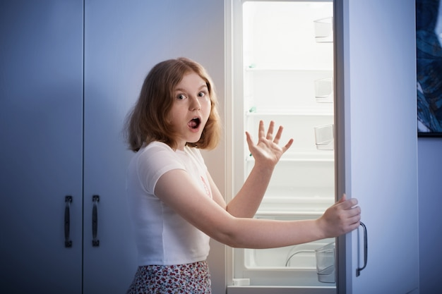 Teen dziewczyna przy pustej lodówce