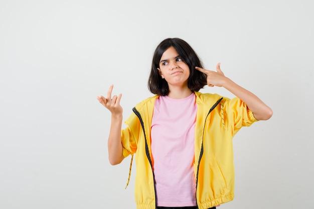 Teen dziewczyna robi gest samobójczy, podnosząc rękę w zdziwionym geście w koszulce, kurtce i patrząc niezdecydowany, widok z przodu.
