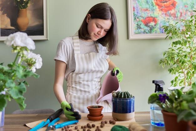Teen dziewczyna sadzi małego kaktusa w doniczce. hobby i wypoczynek, ogrodnictwo w domu, rośliny doniczkowe, miejska dżungla w mieszkaniu, koncepcja przyjaciół doniczkowych