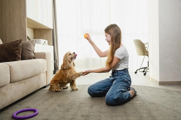 Teen dziewczyna siedzi na dywanie i gra z cocker spanielem w okresie izolacji.
