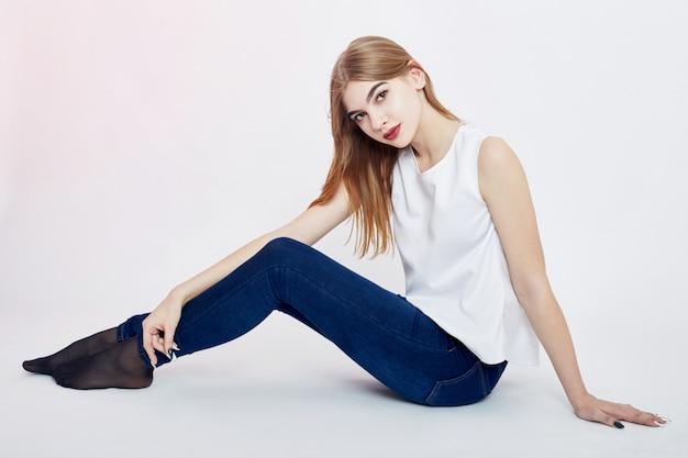 Teen dziewczyna siedzi na podłodze i marzy, długie włosy