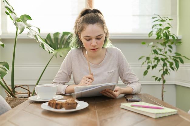 Teen dziewczyna siedzi w domu przy stole, pisanie lekcji przy użyciu smartfona do nauki