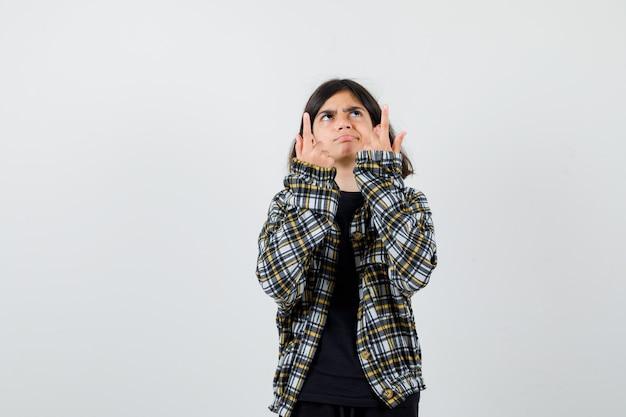 Teen dziewczyna skierowana w górę, patrząc w górę w casual shirt i patrząc niezdecydowany. przedni widok.