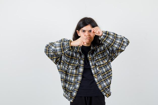 Teen dziewczyna stojąca w pozie walki w casual shirt i patrząc wściekły. przedni widok.