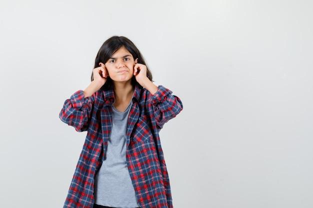 Teen dziewczyna trzyma pięści na policzkach w kraciastej koszuli i ponury, widok z przodu.