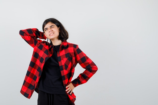 Teen dziewczyna trzyma rękę za głową w t-shirt, kraciaste koszule i bolesny wygląd. przedni widok.