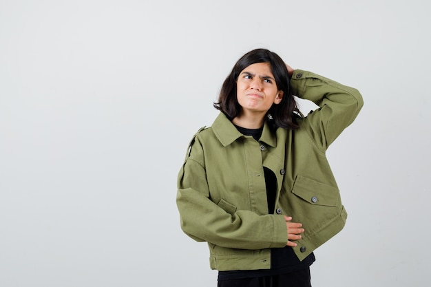 Teen dziewczyna trzyma rękę za głową w t-shirt, kurtkę i szukam miło. przedni widok.