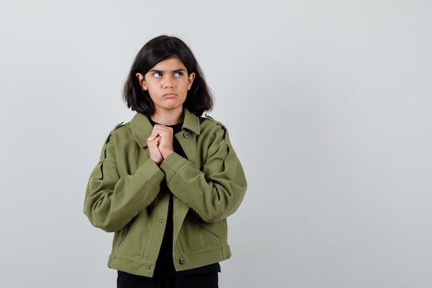 Teen dziewczyna trzyma splecione ręce na klatce piersiowej w t-shirt, zieloną kurtkę i patrząc zamyślony, widok z przodu.