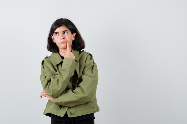 Teen dziewczyna trzymając palec w pobliżu ust w koszulce, zielonej kurtce i patrząc skupiony, widok z przodu.