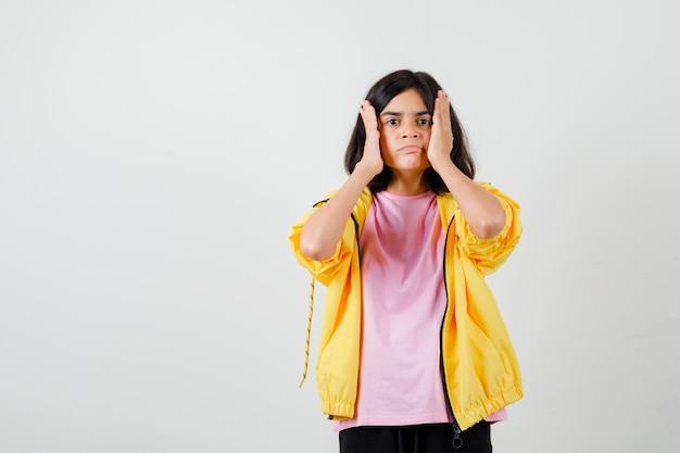 Teen dziewczyna trzymając ręce w pobliżu twarzy w koszulce, kurtce i patrząc skupiony, widok z przodu.