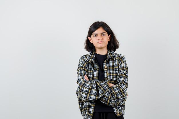 Teen dziewczyna trzymając ręce złożone w casual shirt i patrząc ponury, widok z przodu.