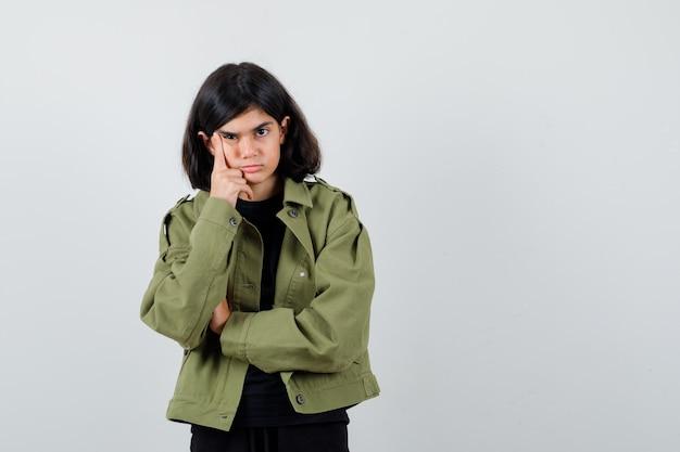 Teen dziewczyna trzymając rękę na policzku w t-shirt, zieloną kurtkę i patrząc zamyślony. przedni widok.