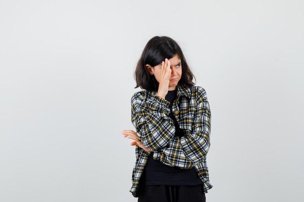 Teen dziewczyna trzymając rękę na twarzy, patrząc na bok w casual shirt i patrząc przestraszony, widok z przodu.