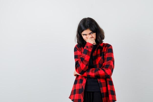 Teen dziewczyna trzymając rękę na ustach w koszuli casual i patrząc zamyślony. przedni widok.
