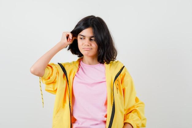 Teen dziewczyna trzymając rękę na uszach w żółtym dresie, koszulce i patrząc zamyślony, widok z przodu.