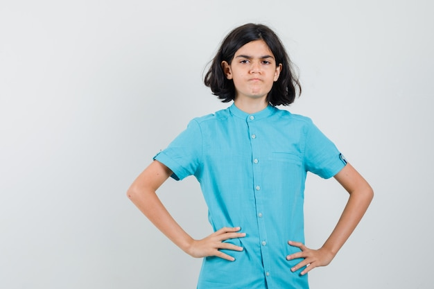 Teen dziewczyna trzymając się za ręce na jej talii w niebieskiej koszuli i patrząc niezadowolony