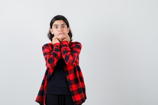 Teen dziewczyna trzymając się za ręce na szyi w t-shirt, kraciaste koszule i patrząc przestraszony. przedni widok.